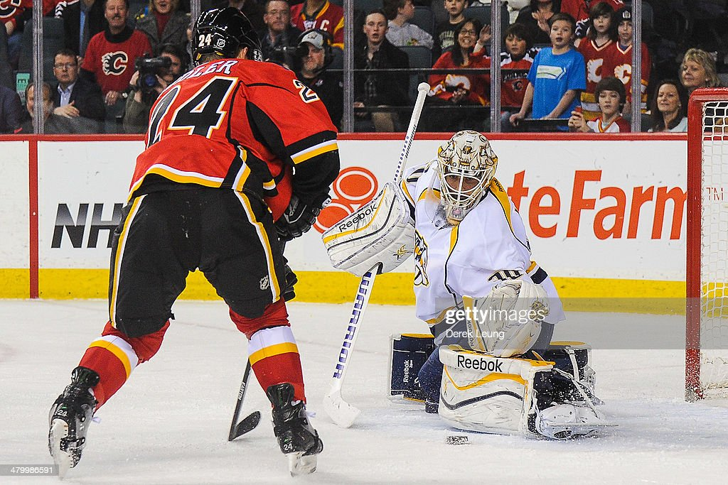 <a gi-track='captionPersonalityLinkClicked' href=/galleries/search?phrase=Jiri+Hudler&family=editorial&specificpeople=2118675 ng-click='$event.stopPropagation()'>Jiri Hudler</a> #24 of the Calgary Flames takes a shot on <a gi-track='captionPersonalityLinkClicked' href=/galleries/search?phrase=Carter+Hutton&family=editorial&specificpeople=6872781 ng-click='$event.stopPropagation()'>Carter Hutton</a> #30 of the Nashville Predators during an NHL game at Scotiabank Saddledome on March 21, 2014 in Calgary, Alberta, Canada. The Predators defeated the Flames 6-5.