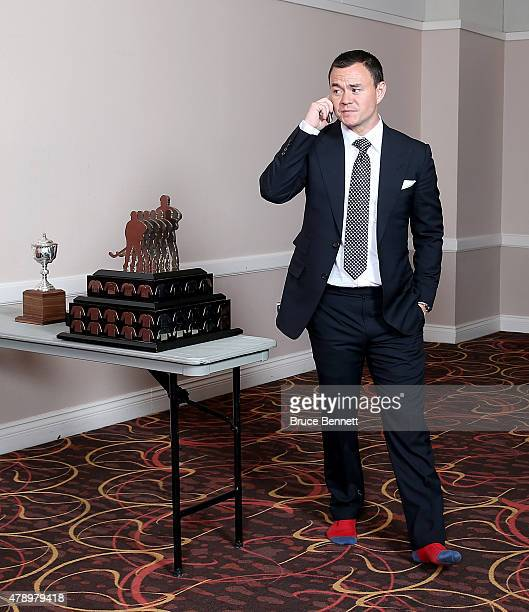 Jiri Hudler of the Calgary Flames talks on the phone with no shoes on in the press room after winning the Lady Byng Trophy at the 2015 NHL Awards at...