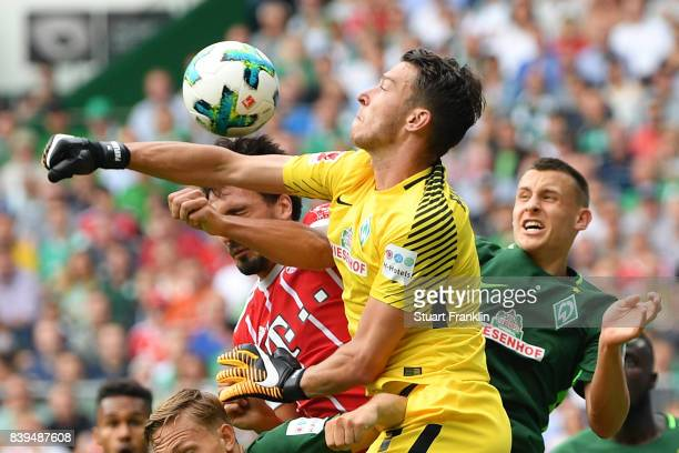 Jiri Pavlenka of Bremen fights for the ball with Mats Hummels of Bayern Muenchen during the Bundesliga match between SV Werder Bremen and FC Bayern...