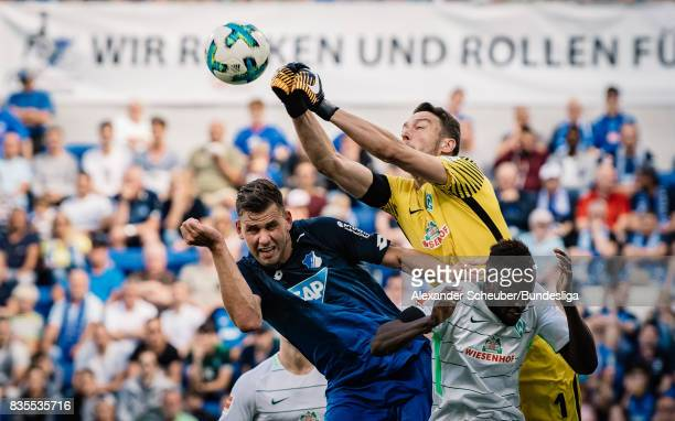 Jiri Pavlenka of Bremen tackles Adam Szalai of Hoffenheim during the Bundesliga match between TSG 1899 Hoffenheim and SV Werder Bremen at Wirsol...