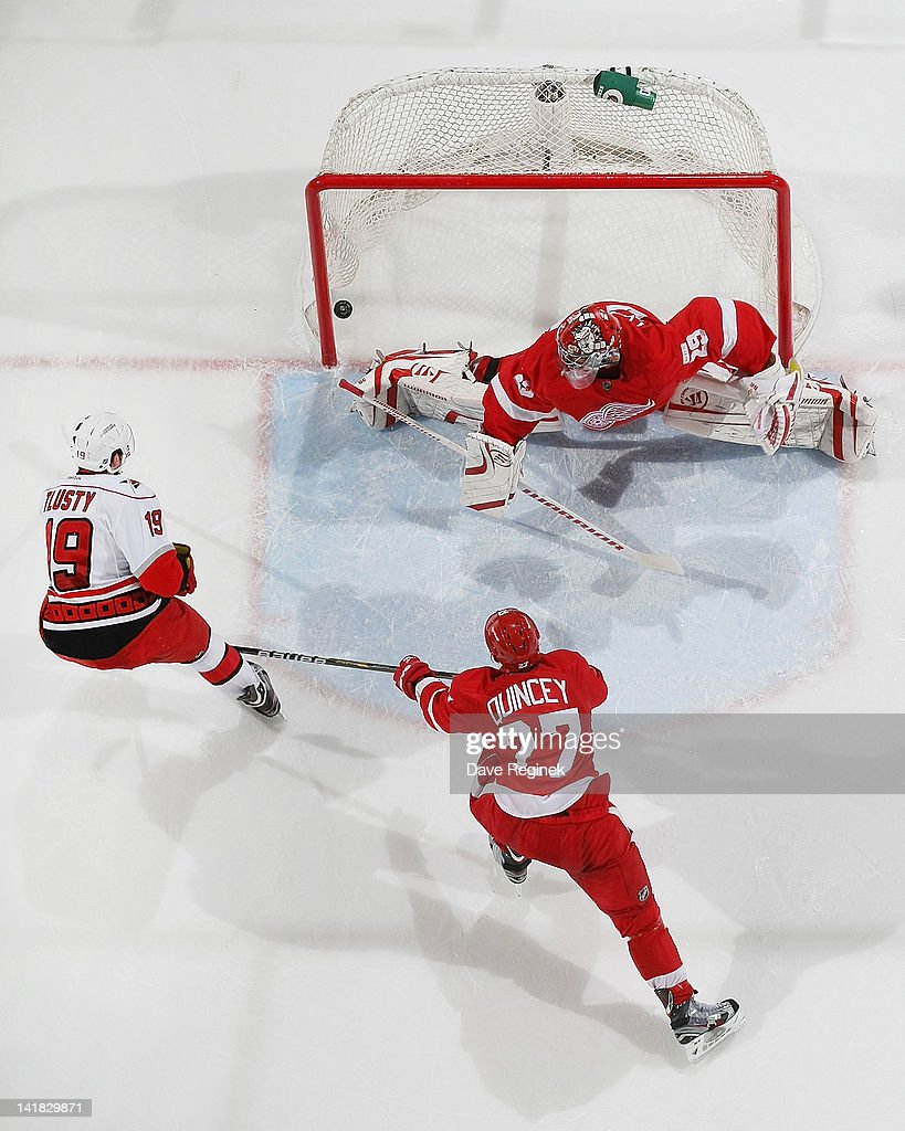 Jiri Tlusty of the Carolina Hurricanes scores a goal on Ty Conklin of the Detroit Red Wings while Kyle Quincey defends during an NHL game at Joe...