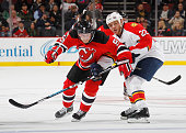 Jiri Tlusty of the New Jersey Devils is held up by Shawn Thornton of the Florida Panthers at the Prudential Center on December 17 2015 in Newark New...