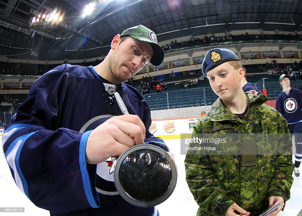 Jiri Tlusty #91 of the Winnipeg Jets signs an autograph for a member of the Canadian Armed Forces following NHL action against the Ottawa Senators for Canadian Armed Forces Appreciation Night on March 4, 2015 at the MTS Centre in Winnipeg, Manitoba, Canada.