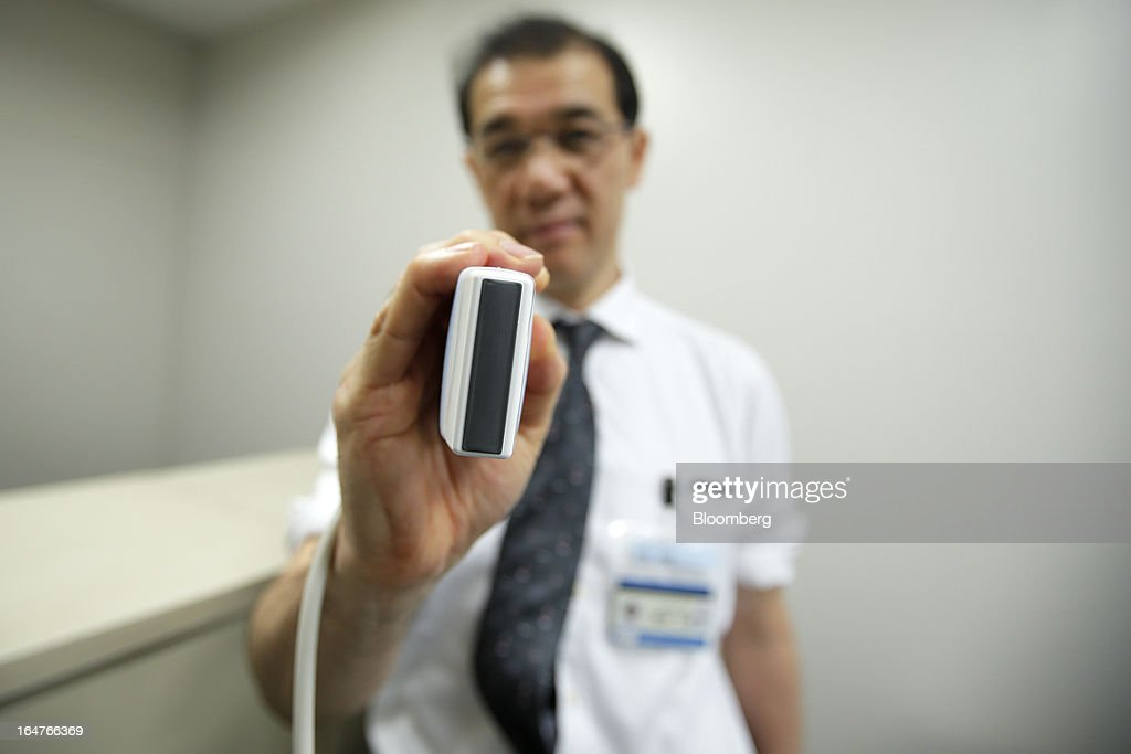 Jiro Maegawa, professor of plastic and reconstructive surgery at Yokohama City University (YCU), displays a home-use ultrasonographic device for breast cancer screening at the university's Advanced Medical Research Center (AMRC) in Yokohama City, Kanagawa Prefecture, Japan, on Monday, March 18, 2013. Japan aims to be a nation with the most advanced medical technologies and healthcare services in the world and to develop the medical industries for the revitalization of the country's economy. Photographer: Kiyoshi Ota/Bloomberg via Getty Images