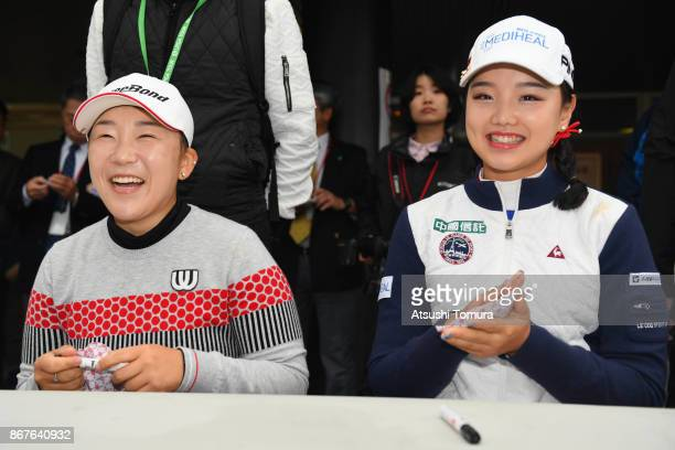 Jiyai Shin of South Korea and Yuting Seki of China attend autograph session after the final day has cancelled because of rain storm during the final...
