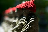 Jizo bodhisattva statues in a row wearing red hats