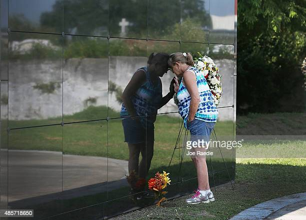 Jo Ann Foster leans against a Mausoleum as she pays her respects at the New Orleans Katrina Memorial where nearly 100 unclaimed or unidentified...