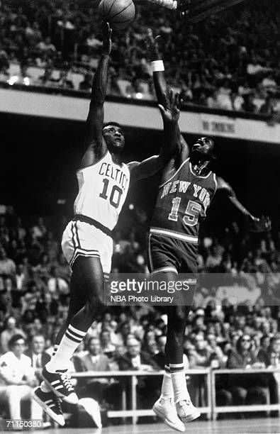 Jo Jo White of the Boston Celtics shoots a layup against Earl Monroe of the New York Knicks during a game circa 19721979 at the Boston Garden in...