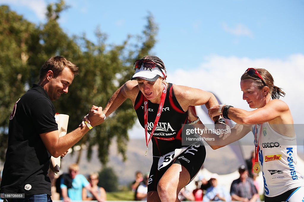 Jo Lawn of Auckland is helped onto the podium by Gina Crawford finishing third in the Challenge Wanaka on January 19, 2013 in Wanaka, New Zealand.