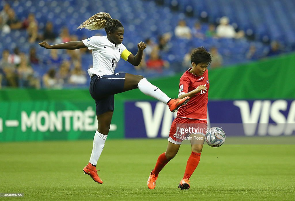 Jo Ryon Hwa (R) of Korea DPR and Griegde Mbock Bathy (L) of France battle for the ball during the FIFA U-20 Women's World Cup 2014 3rd place playoff match between Korea DPR and France at Olympic Stadium on August 24, 2014 in Montreal, Canada.