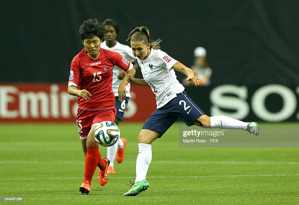 Jo Ryon Yong (L) of Korea DPR and Eve Perisset (R) of France battle for the ball during the FIFA U-20 Women's World Cup 2014 3rd place playoff match between Korea DPR and France at Olympic Stadium on August 24, 2014 in Montreal, Canada.