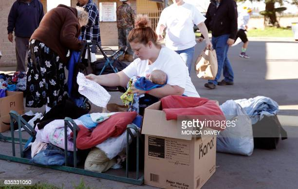 Jo Spiger from Oroville holds her nephew as she looks through donated clothing for him at the Silver Dollar Fairgrounds in Chico California on...