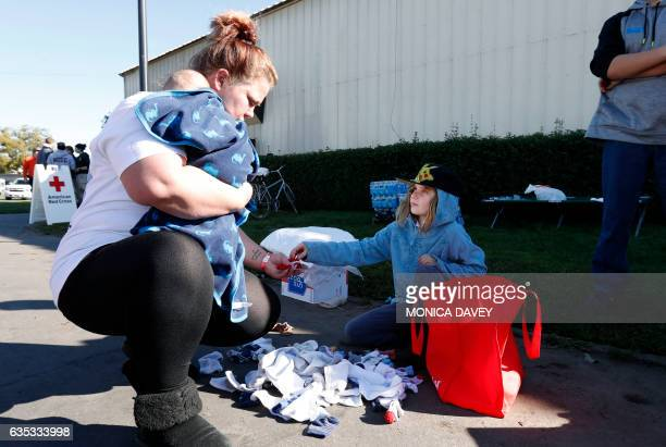 Jo Spiger from Oroville holds her nephew as she looks through donated socks given to her by Jill Johnston from Chico who is volunteering at the...