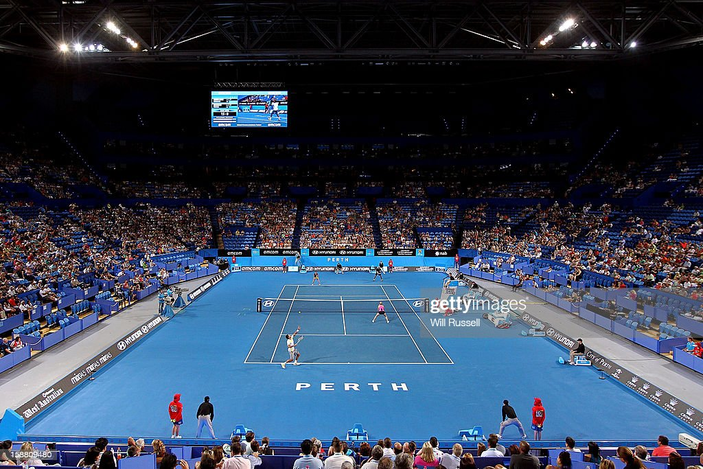 Jo Wilfried Tsonga of France serves as Mathilde Johansson looks on in the mixed doubles match against Fernando Verdasco and Anabel Medina Garrigues of Spain during day two of the Hopman Cup at Perth Arena on December 30, 2012 in Perth, Australia.