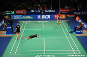 Joachim Fischer Nielsen of Denmark falls during semifinals match against Xu Chen and Ma Jin of China in the 2015 BCA Indonesia Open at Istora Senayan...