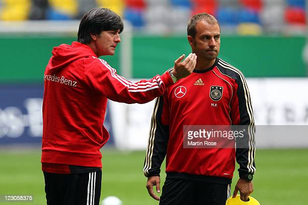 Joachim Loew head coach of Germany speaks to assistant coach Hansi Flick during the German National Team training session at esprit Arena on August...
