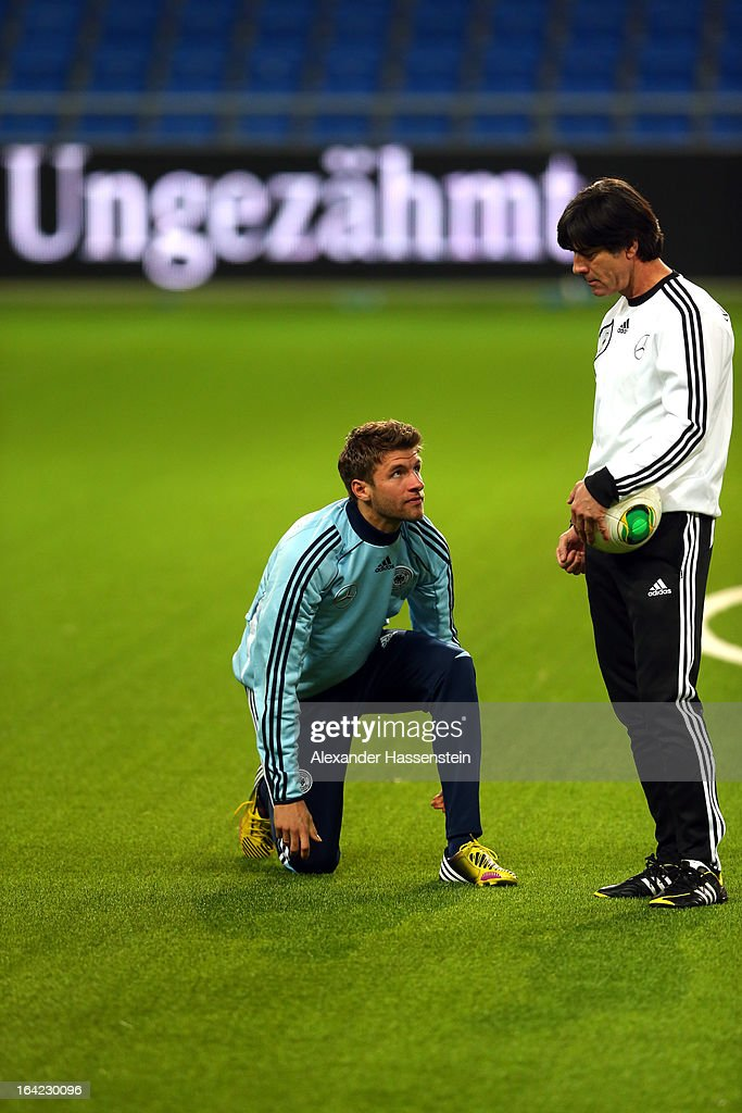 Joachim Loew, head coach of the German national football team talks to his palyer Thomas Mueller during a training session at Astana arena on March 21, 2013 in Astana, Kazakhstan.
