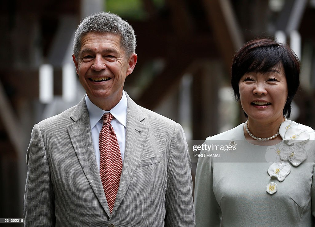 Joachim Sauer (L), husband of German Chancellor Angela Merkel and Akie Abe, wife of Japanese Prime Minister Shinzo Abe, exhange smiles as they pose for a photograph next to Ujibashi bridge during a visit to Ise-Jingu Shrine in the city of Ise in Mie prefecture, on May 26, 2016 on the first day of the G7 leaders summit. World leaders kick off two days of G7 talks in Japan on May 26 with the creaky global economy, terrorism, refugees, China's controversial maritime claims, and a possible Brexit headlining their packed agenda. / AFP / POOL / TORU