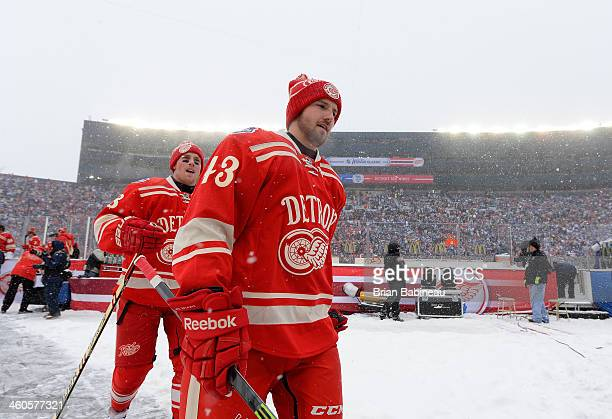Joakim Andersson and Darren Helm of the Detroit Red Wings walk back to the locker after warmup prior to the 2014 Bridgestone NHL Winter Classic on...