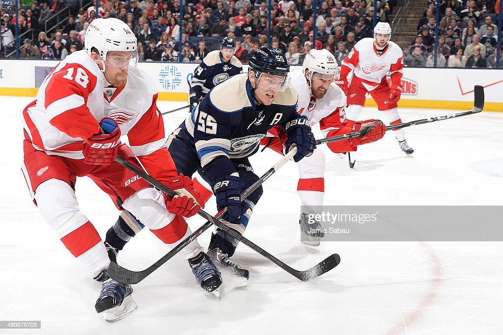 Joakim Andersson #18 and <a gi-track='captionPersonalityLinkClicked' href=/galleries/search?phrase=Niklas+Kronwall&family=editorial&specificpeople=220826 ng-click='$event.stopPropagation()'>Niklas Kronwall</a> #55 of the Detroit Red Wings and <a gi-track='captionPersonalityLinkClicked' href=/galleries/search?phrase=Mark+Letestu&family=editorial&specificpeople=4601071 ng-click='$event.stopPropagation()'>Mark Letestu</a> #55 of the Columbus Blue Jackets skate after a loose puck during the third period on March 25, 2014 at Nationwide Arena in Columbus, Ohio. Columbus defeated Detroit 4-2.