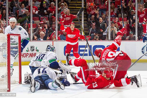 Joakim Andersson of the Detroit Red Wings celebrates his goal with teammates Pavel Datsyuk and Danny DeKeyser in front of goaltender Ryan Miller of...
