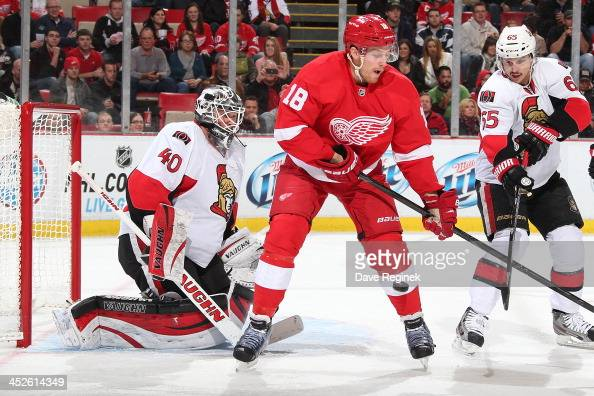 Joakim Andersson of the Detroit Red Wings looks to deflect the puck in front of Robin Lehner Erik Karlsson of the Ottawa Senators during an NHL game...