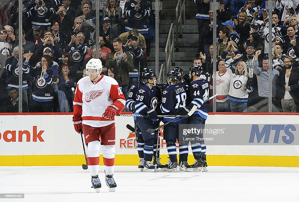 Joakim Andersson #18 of the Detroit Red Wings skates away as Winnipeg Jets players celebrate a third period goal by Andrew Ladd #16 (not seen) at the MTS Centre on November 4, 2013 in Winnipeg, Manitoba, Canada.