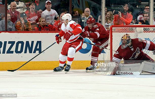 Joakim Andersson of the Detroit Red Wings skates with the puck behind goaltender Mike Smith of the Arizona Coyotes as Andrew Campbell of the Coyotes...