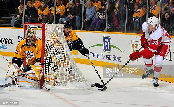 Joakim Andersson of the Detroit Red Wings tries to get the puck in front of goalie Pekka Rinne of the Nashville Predators at Bridgestone Arena on...