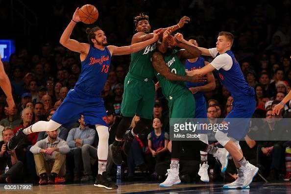 Joakim Noah and Kristaps Porzingis of the New York Knicks pursue the loose ball against Marcus Smart and Amir Johnson of the Boston Celtics at...