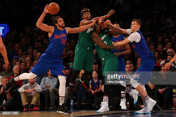 Joakim Noah and Kristaps Porzingis of the New York Knicks pursue the loose ball against Marcus Smart and Amir Johnson of the Boston Celtics at...