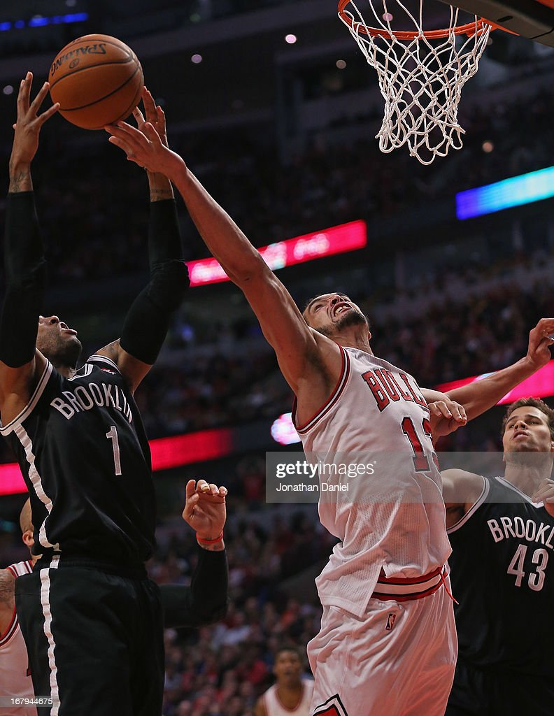 Joakim Noah #13 of the Chicago Bulls and C.J. Watson #1 of the Brooklyn Nets grab for a rebound in Game Six of the Eastern Conference Quarterfinals during the 2013 NBA Playoffs at the United Center on May 2, 2013 in Chicago, Illinois. The Nets defeated the Bulls 95-92.