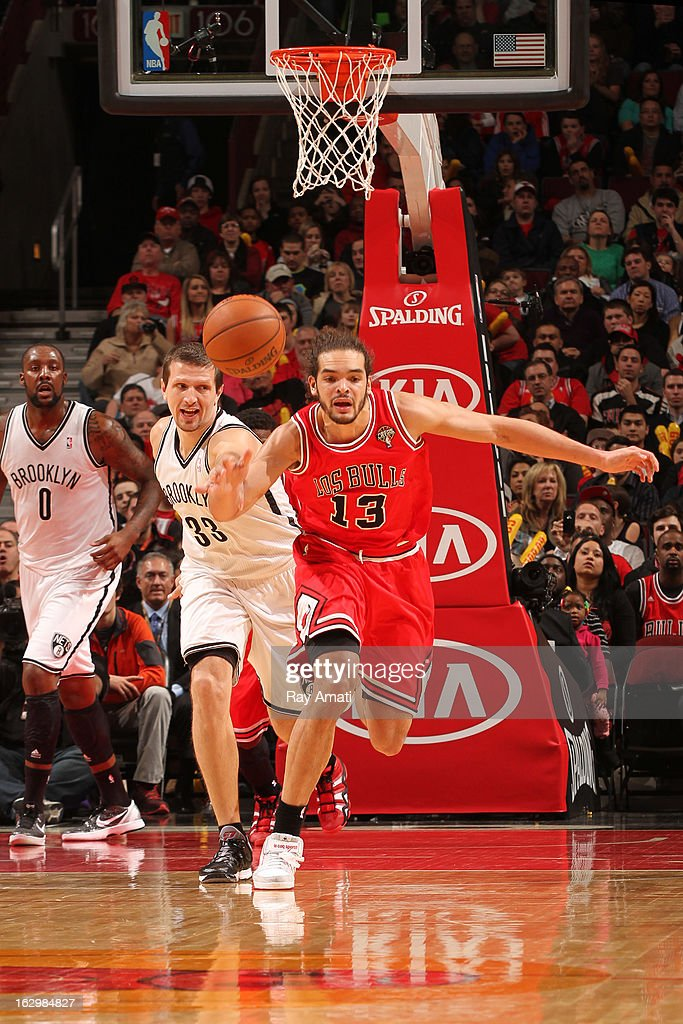 Joakim Noah #13 of the Chicago Bulls batlles for a loose ball against Mirza Teletovic #33 of the Brooklyn Nets on March 2, 2013 at the United Center in Chicago, Illinois.