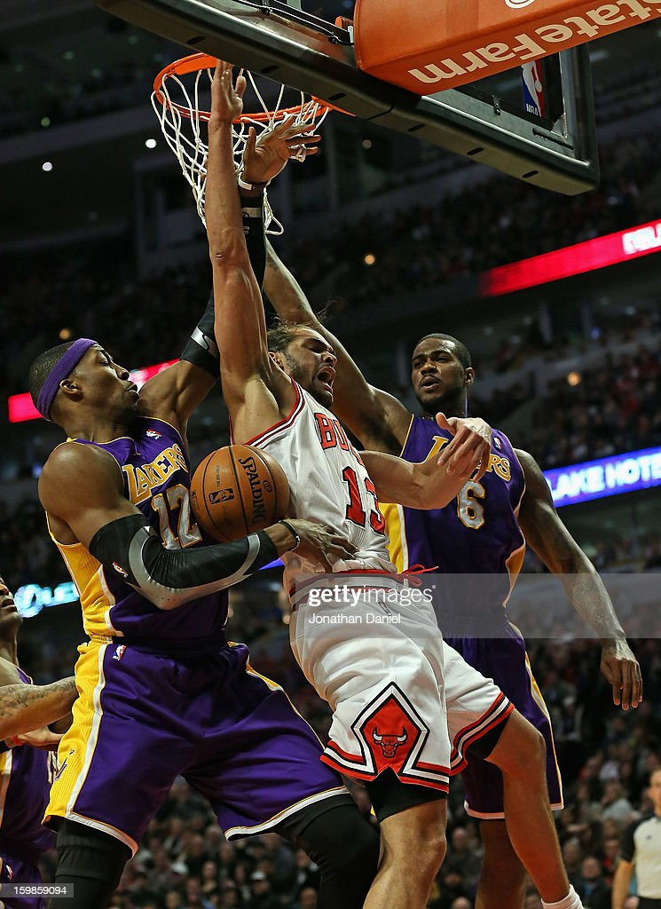 Joakim Noah #13 of the Chicago Bulls battles for a rebound with Dwight Howard #12 (L) and Earl Clark #6 of the Los Angeles Lakers at the United Center on January 21, 2013 in Chicago, Illinois. The Bulls defeated the Lakers 95-83.