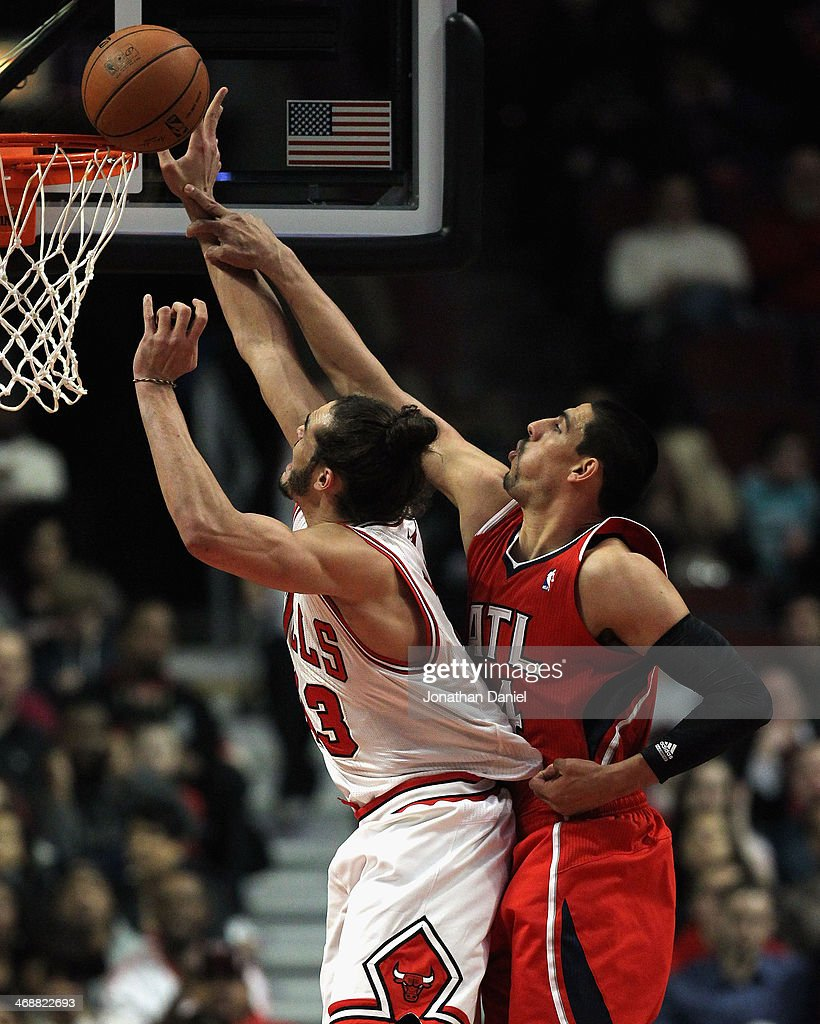 Joakim Noah #13 of the Chicago Bulls battles for a rebound with Gustavo Ayon #14 of the Atlanta Hawks at the United Center on February 11, 2014 in Chicago, Illinois. The Bulls defeated the Hawks 100-85.
