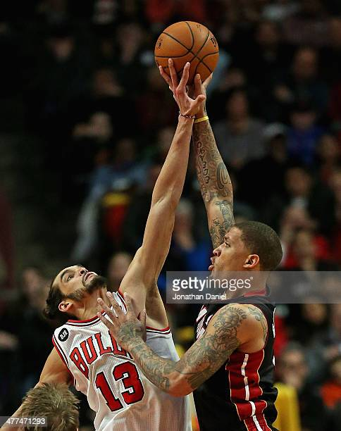 Joakim Noah of the Chicago Bulls blocks a shot by Michael Beasley of the Miami Heat at the United Center on March 9 2014 in Chicago Illinois The...