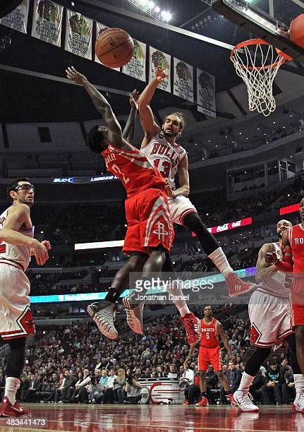Joakim Noah of the Chicago Bulls blocks a shot by Patrick Beverly of the Houston Rockets at the United Center on March 13 2014 in Chicago Illinois...