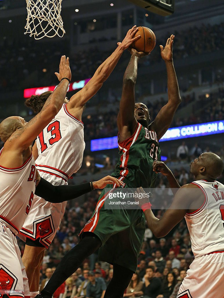 Joakim Noah #13 of the Chicago Bulls blocks a shot by Samuel Dalembert #21 of the Milwaukee Bucks as he tries to shoot over Loul Deng #9 and Carlos Boozer #5 at the United Center on November 26, 2012 in Chicago, Illinois.