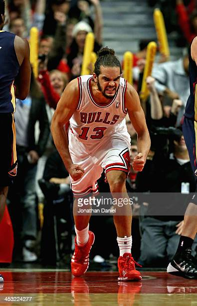 Joakim Noah of the Chicago Bulls celebrates after a dunk against the New Orleans Pelicans at the United Center on December 2 2013 in Chicago Illinois...