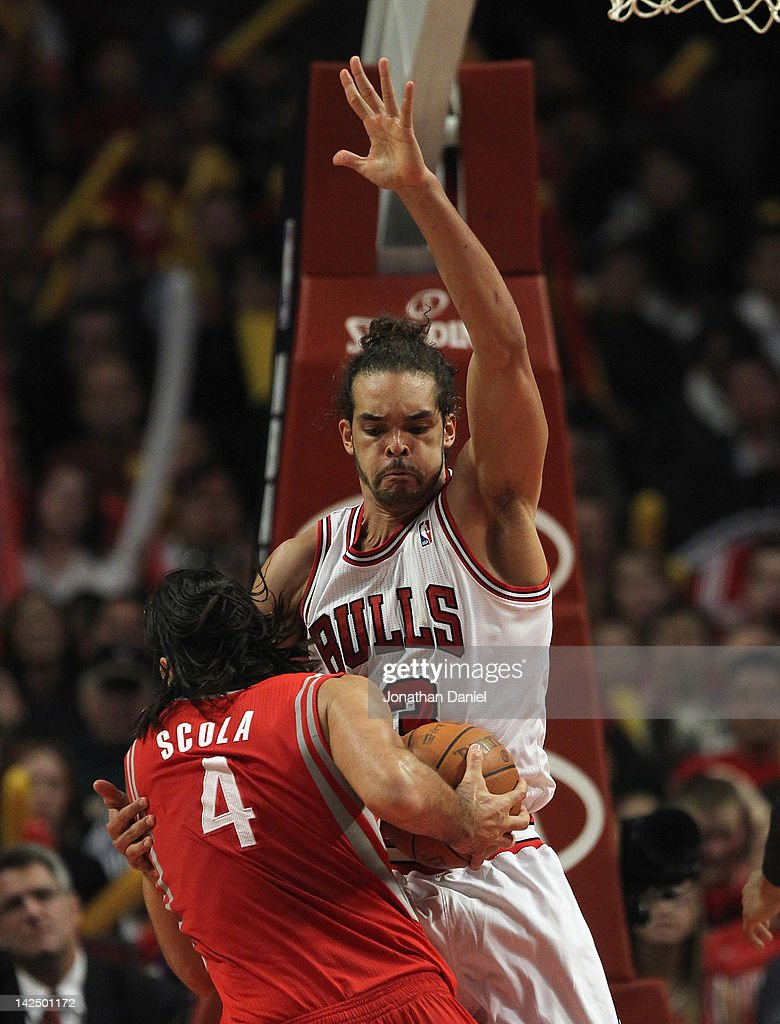 Joakim Noah #13 of the Chicago Bulls defends against Luis Scola #4 of the Houston Rockets at the United Center on April 2, 2012 in Chicago, Illinois. The Rockets defeated the Bulls 99-93.