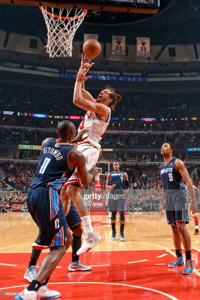 Joakim Noah #13 of the Chicago Bulls drives to the basket against Bismack Biyombo #0 of the Charlotte Bobcats on January 28, 2013 at the United Center in Chicago, Illinois.