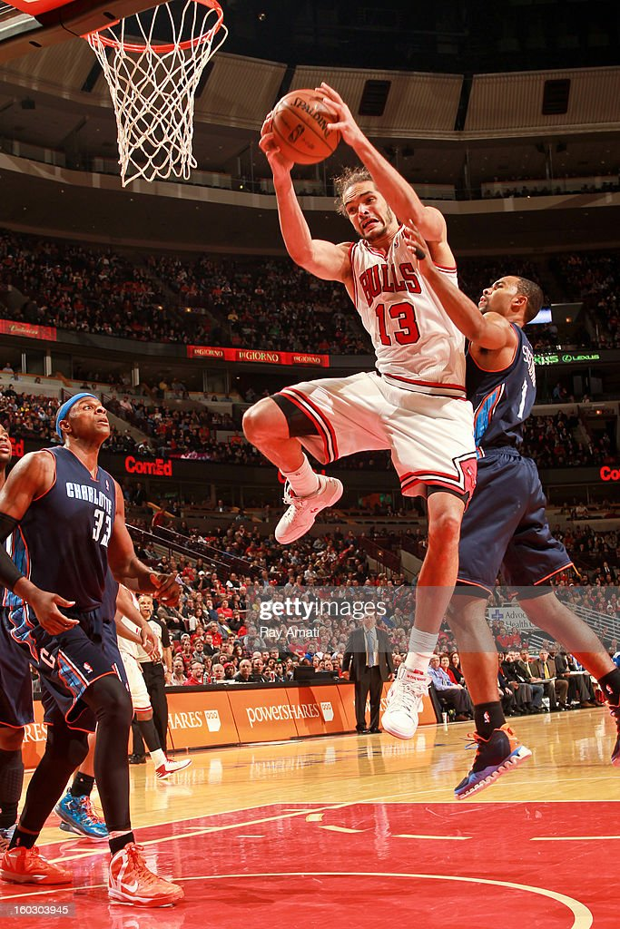 Joakim Noah #13 of the Chicago Bulls drives to the basket against Ramon Sessions #7 of the Charlotte Bobcats on January 28, 2013 at the United Center in Chicago, Illinois.