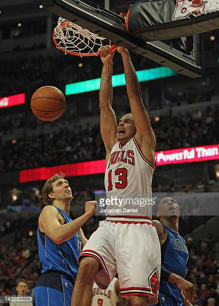 Joakim Noah of the Chicago Bulls dunks over Dirk Nowitzki and Shawn Marion of the Dallas Mavericks at the United Center on April 21 2012 in Chicago...