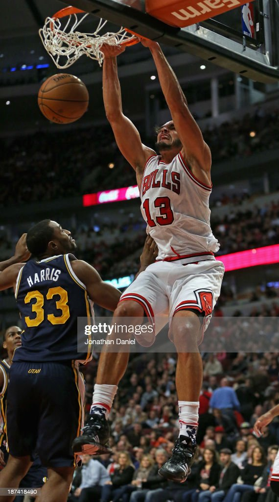 Joakim Noah #13 of the Chicago Bulls dunks over Mike Harris #33 of the Utah Jazz at the United Center on November 8, 2013 in Chicago, Illinois.