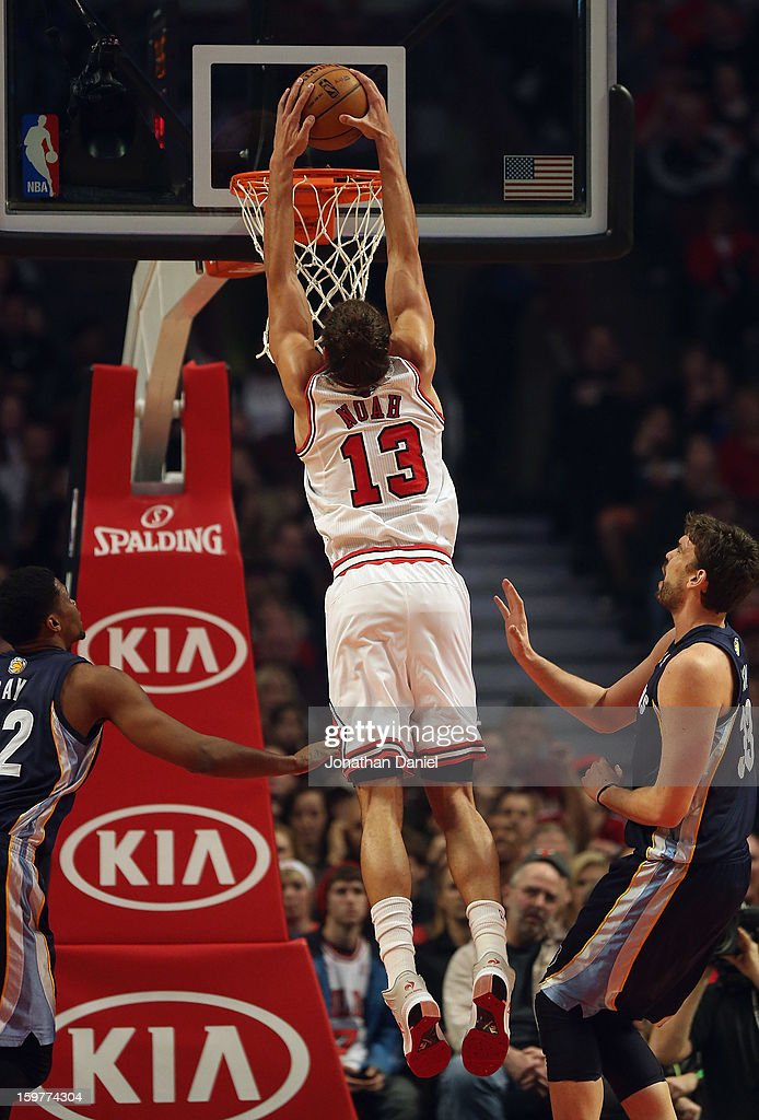 Joakim Noah #13 of the Chicago Bulls dunks over Rudy Gay #22 (L) and Marc Gasol #33 of the Memphis Grizzles at the United Center on January 19, 2013 in Chicago, Illinois. The Grizzlies defeated the Bulls 85-82 in overtime.