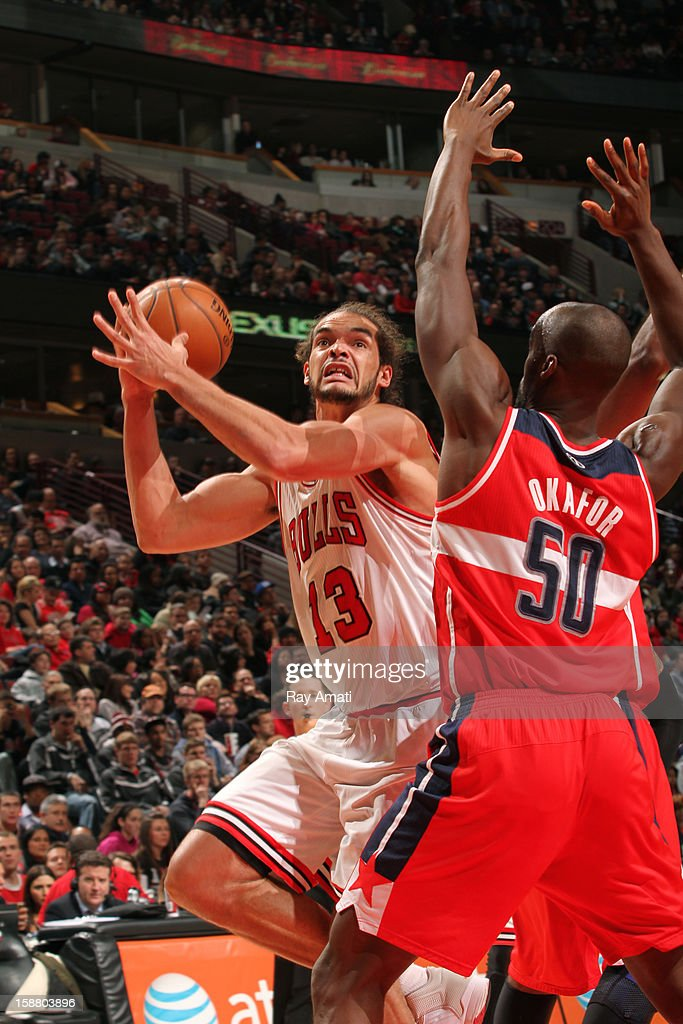 Joakim Noah #13 of the Chicago Bulls goes to the basket against Emeka Okafor #50 of the Washington Wizards on December 29, 2012 at the United Center in Chicago, Illinois.