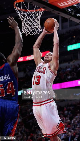Joakim Noah of the Chicago Bulls goes up for a dunk against Jason Maxiell of the Detroit Pistons at the United Center on March 30 2012 in Chicago...
