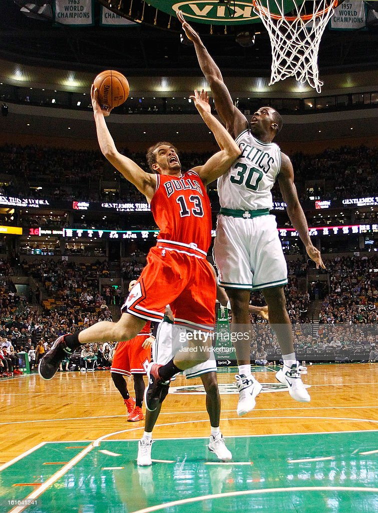 Joakim Noah #13 of the Chicago Bulls goes up for a layup in front of Brandon Bass #30 of the Boston Celtics during the game on February 13, 2013 at TD Garden in Boston, Massachusetts.