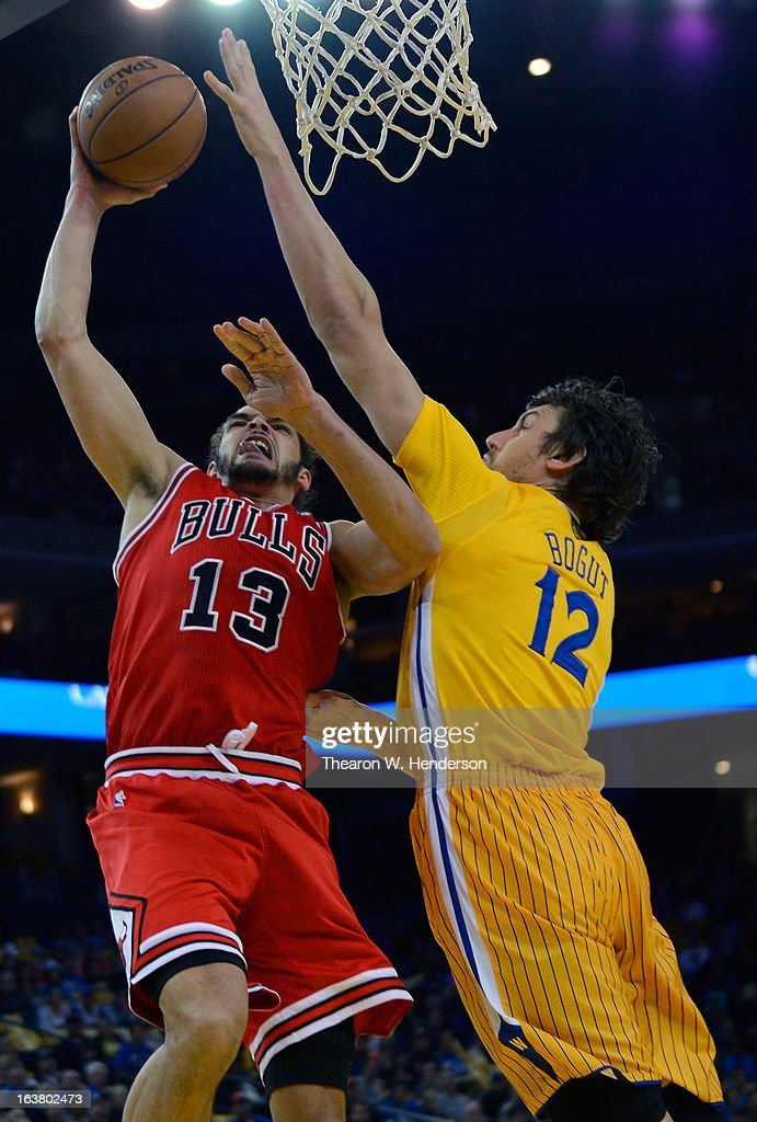 Joakim Noah #13 of the Chicago Bulls goes up to shoot over Andrew Bogut #12 of the Golden State Warriors at Oracle Arena on March 15, 2013 in Oakland, California.