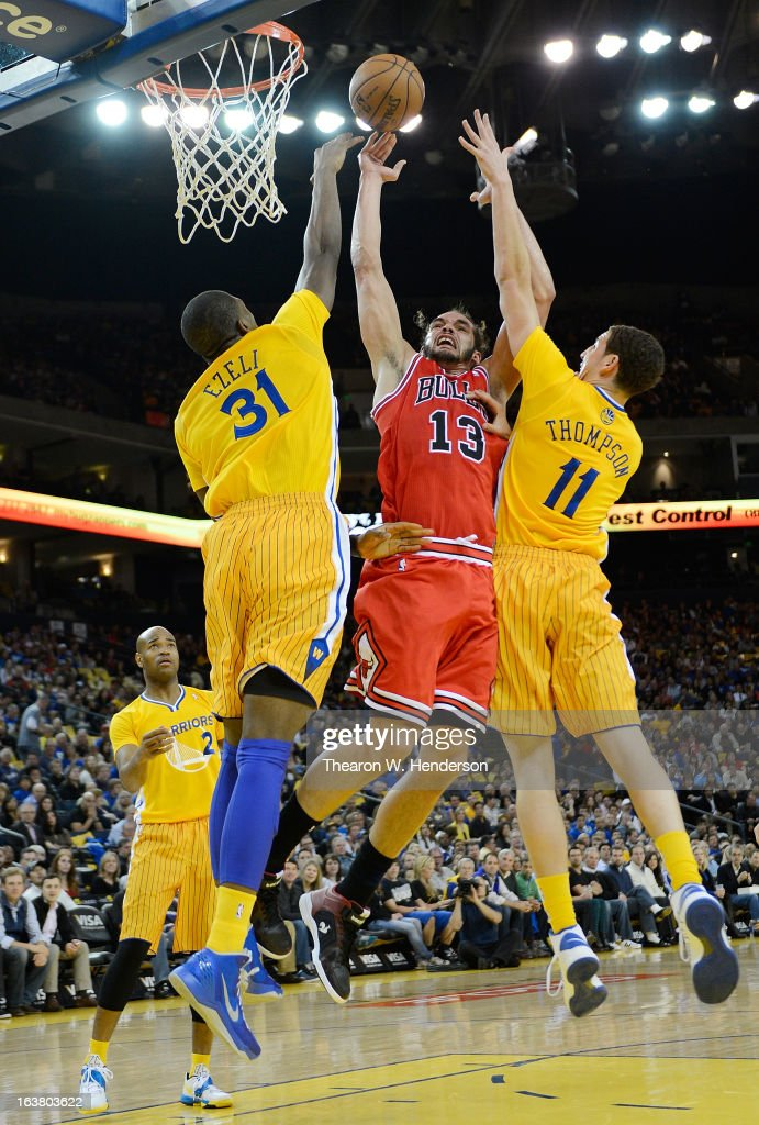 Joakim Noah #13 of the Chicago Bulls goes up to shoot over Klay Thompson #11 and Festus Ezeli #31 of the Golden State Warriors at Oracle Arena on March 15, 2013 in Oakland, California.